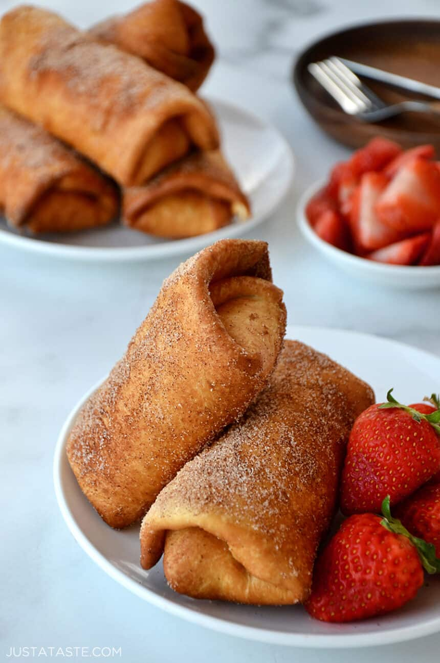 Two Strawberry Cheesecake Chimichangas on a white plate with fresh strawberries