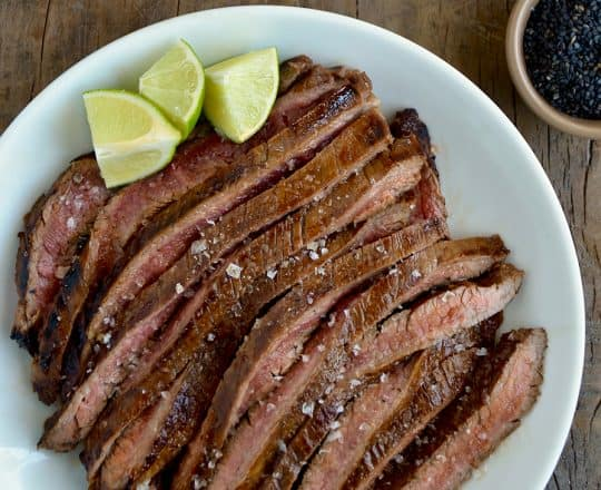 Sliced flank steak with the Ultimate Asian Flank Steak Marinade on white serving plate and lime wedges