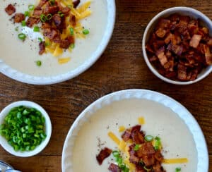 Top-down view of two white bowls containing Loaded Baked Potato Soup garnished with bacon, cheddar cheese and chopped scallions