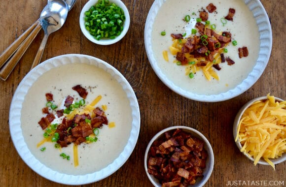 Top-down view of two bowls containing Loaded Baked Potato Soup topped with crispy bacon, sour cream, cheddar cheese and chopped scallions next to three small bowls containing shredded cheddar cheese, chopped bacon and scallions