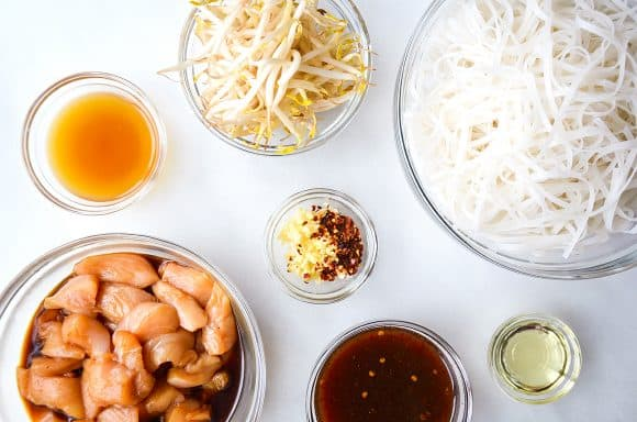 Various sizes of bowls containing bean sprouts, rice noodles, spices, soy sauce, diced chicken and chicken stock