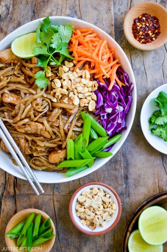 Easy Pad Thai with Chicken on a plate with chopsticks, cilantro, shredded carrots, shredded purple cabbage, scallions and peanuts