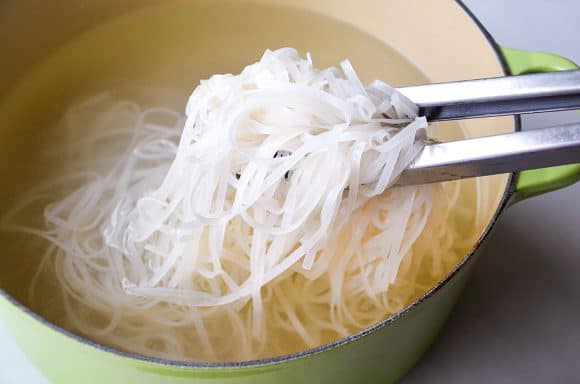 Tongs holding rice noodles over large stockpot