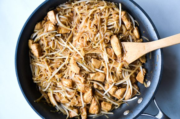 Wooden spoon in skillet with bean sprouts, rice noodles and diced chicken