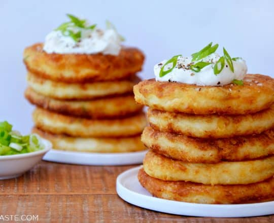 Stacks of mashed potato pancakes on white plates and a small bowl of scallions