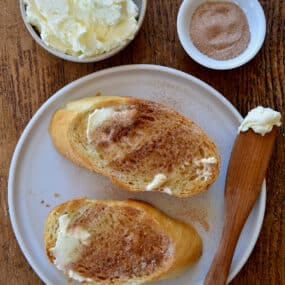 A top-down view of slices of cinnamon-sugar toast with a small bowl of butter
