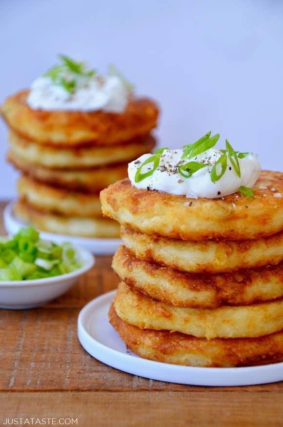 Stacks of mashed potato pancakes topped with sour cream and scallions