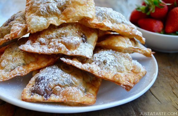 A white plate containing chocolate wontons covered with powdered sugar