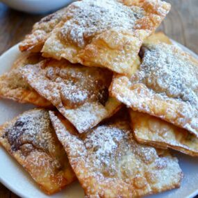 A white plate containing a pile of chocolate wontons covered with powdered sugar
