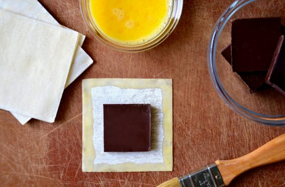 A cutting board with wonton wrappers, chocolate, an egg wash and a pastry brush