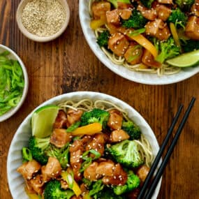 A top-down view of two bowls containing 30-Minute Chicken and Broccoli Stir-Fry and chopsticks