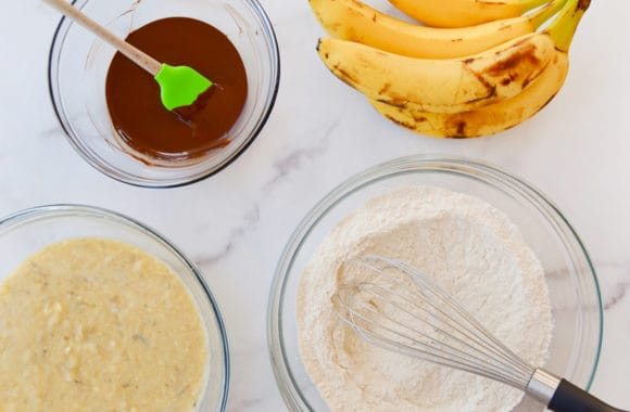 Bowl containing melted chocolate with spatula next to bunch of bananas, bowl with dry ingredients and whisk, and bowl with mashed bananas