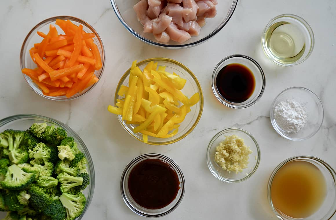 Various sizes of clear bowls containing stir-fry ingredients