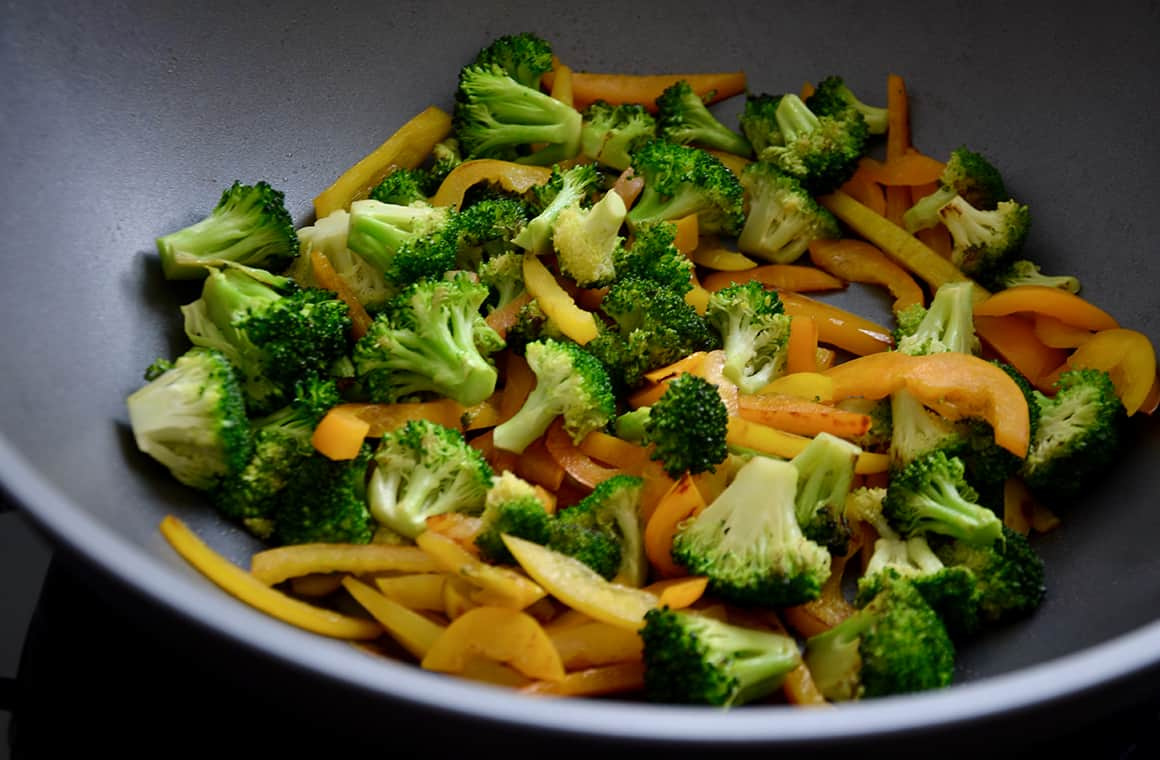 A wok containing yellow and orange pepper strips, and broccoli florets