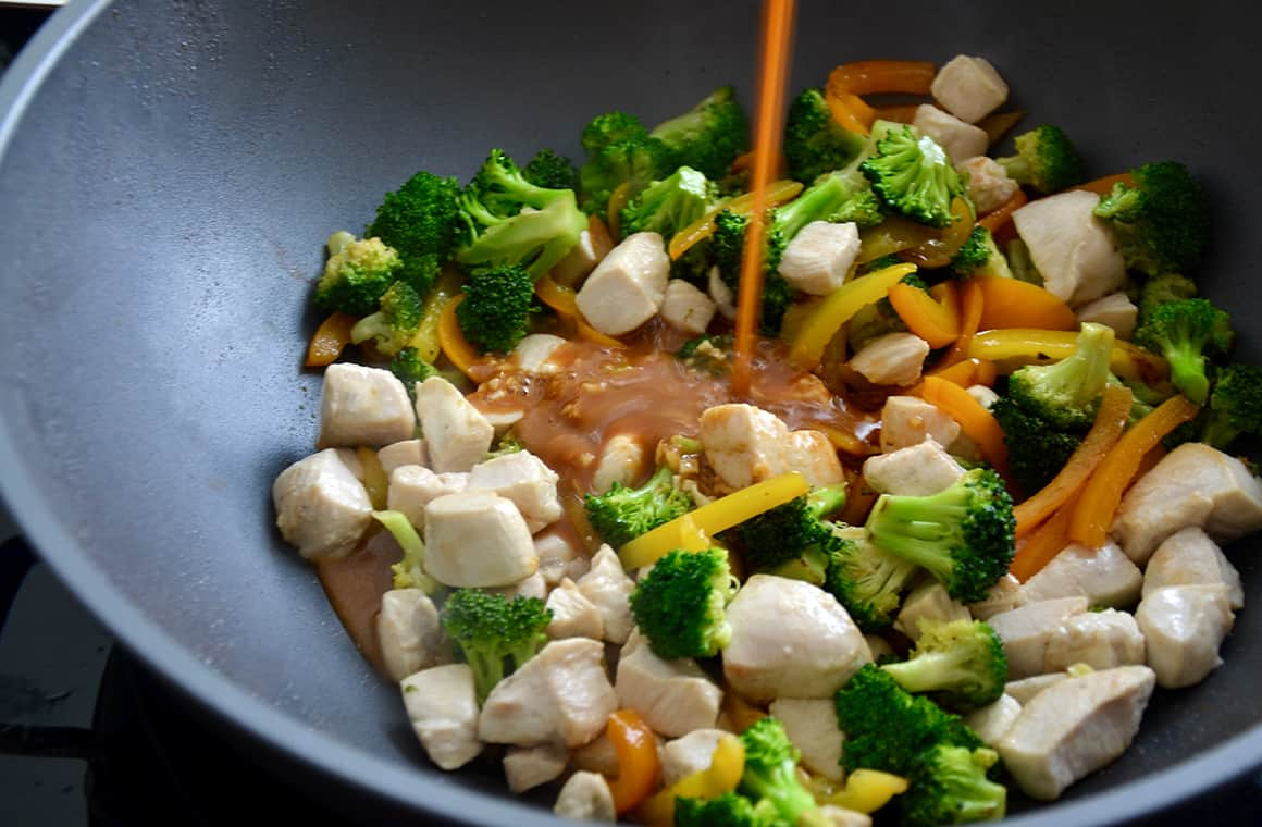 Sauce being poured over vegetables in a wok