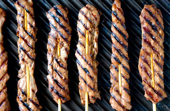 A grill pan with beef skewers on sticks