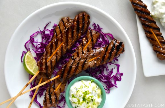 A white plate containing purple shredded cabbage and beef kabobs on skewers