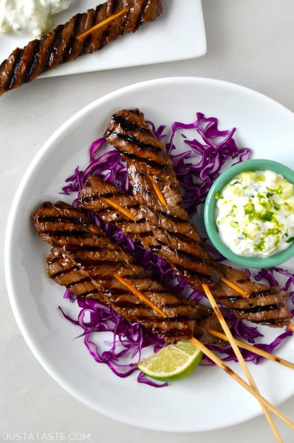 A circular white plate with purple cabbage, beef skewers and yogurt dip