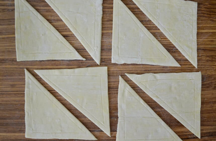 Triangles of puff pastry on a wooden cutting board
