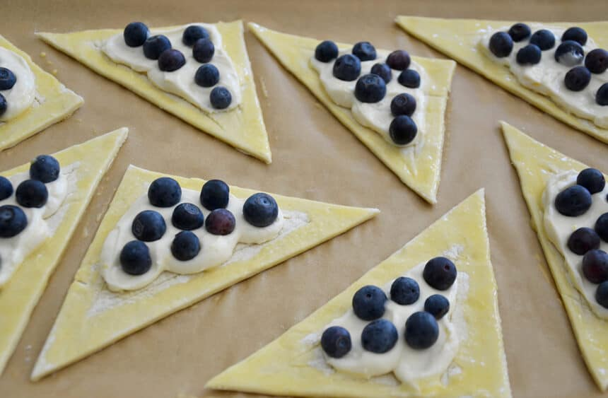 Unbaked triangles of puff pastry topped with lemony cream cheese and fresh blueberries