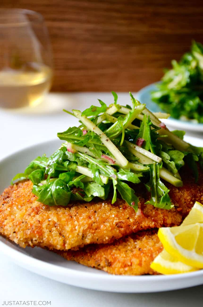Chicken Milanese with Green Apple Salad on a white dinner plate with lemon wedges