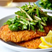 Chicken Milanese (breaded chicken cutlets) on a white plate topped with green apple and arugula salad.