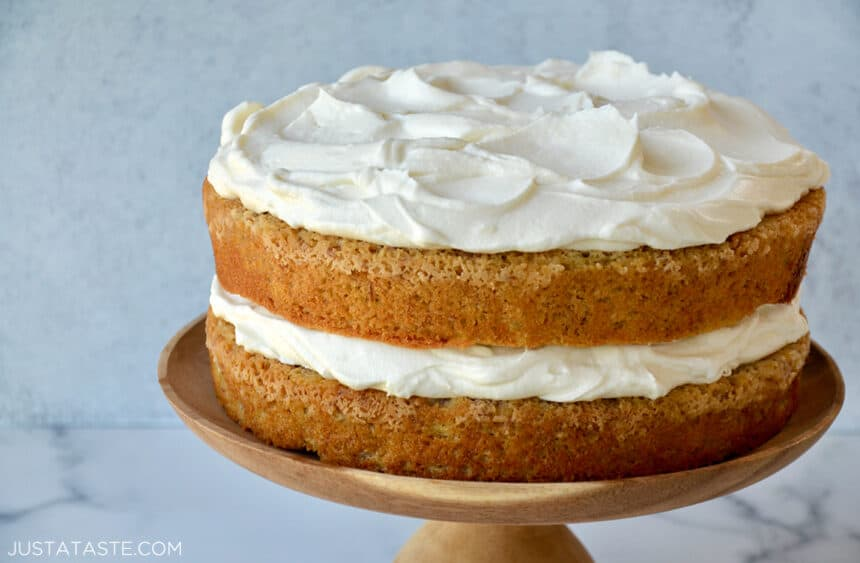 The Best Banana Cake with Cream Cheese Frosting on a wooden cake stand