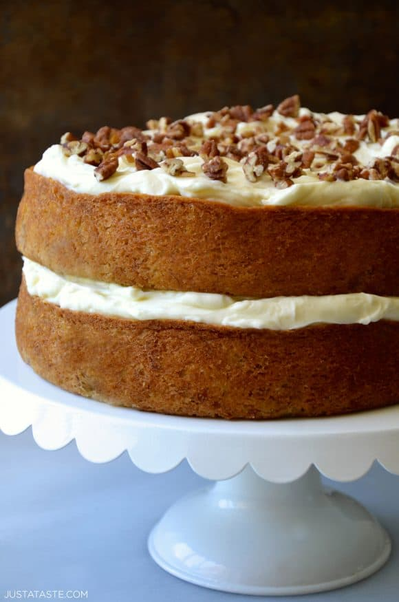 Two-Layer moist banana cake with tangy cream cheese frosting topped with pecans on cake stand