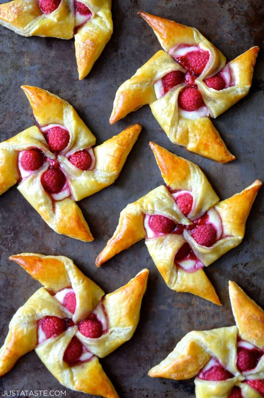 A top-down view of Raspberry Cream Cheese Pinwheel Pastries on a dark surface