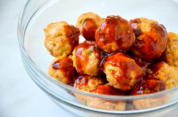 Teriyaki sauce over meatballs in clear mixing bowl