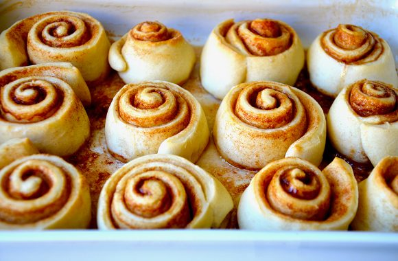 Baked cinnamon rolls close up in a white baking pan