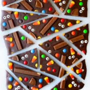 Broken pieces of Halloween Candy Bark on a white surface.