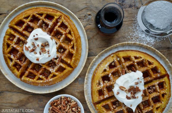 Pumpkin Spice Waffles sprinkled with powdered sugar topped with maple syrup, whipped cream and chopped pecans