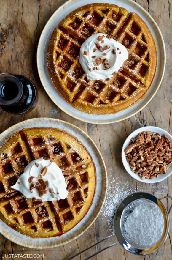 Two Pumpkin Spice Waffles dusted with confectioners' sugar topped with maple syrup, whipped cream and chopped pecans
