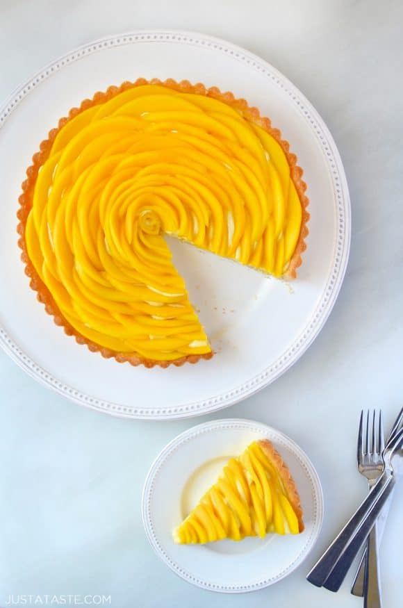 Sliced mango tart with vanilla bean pastry cream next to two forks