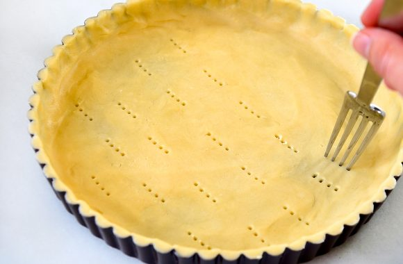 Fork pricking holes all over unbaked crust