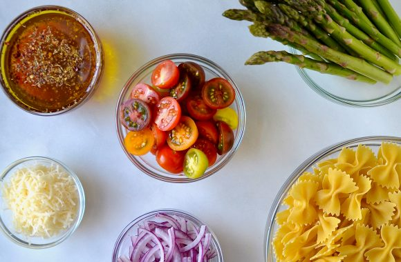 Various sizes of clear bowls containing italian dressing, halved cherry tomatoes, asparagus, bow tie pasta, sliced red onion and parmesan cheese