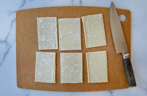 Cutting board containing six rectangles of cut puff pastry next to a sharp knife