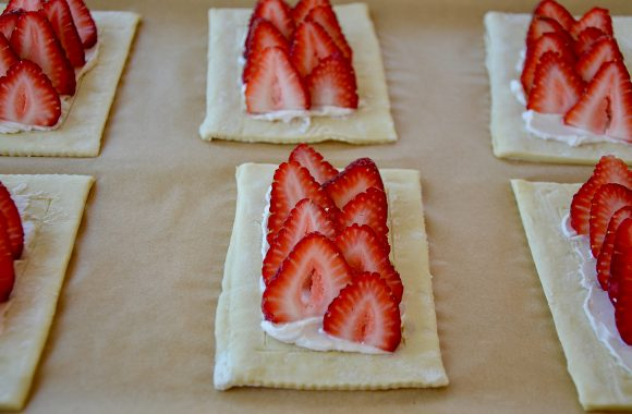 Sliced strawberries in rows on top of cream cheese pastry