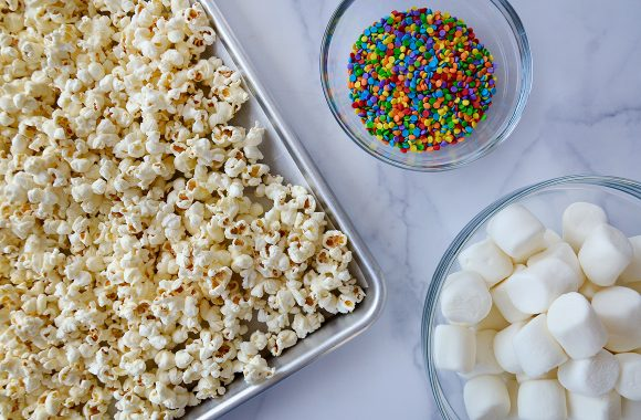 Baking sheet with popcorn next to a small bowl with sprinkles and a large bowl with marshmallows