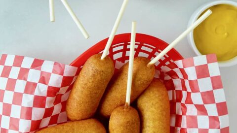 Red food basket filled with Easy Homemade Mini Corn Dogs next to small ramekins with ketchup and mustard