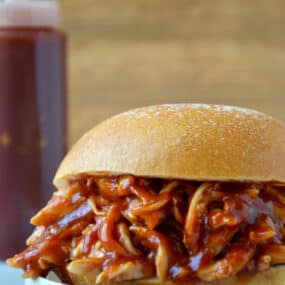 Pulled pork doused in Easy Homemade Root Beer Barbecue Sauce sandwiched between two hamburger bun halves.