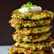 Tall stack of 5-ingredient zucchini fritters topped with sour cream and scallions