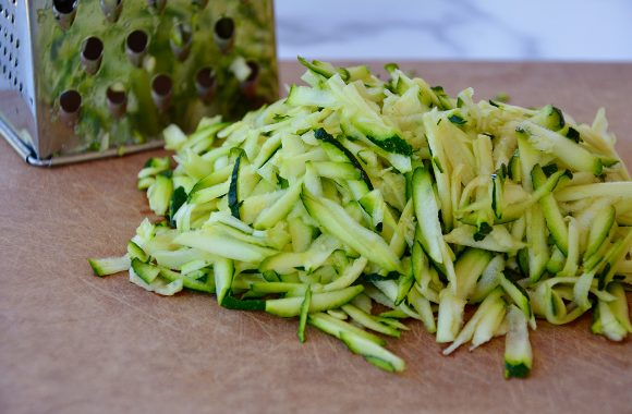 Shredded zucchini on cutting board with box grater