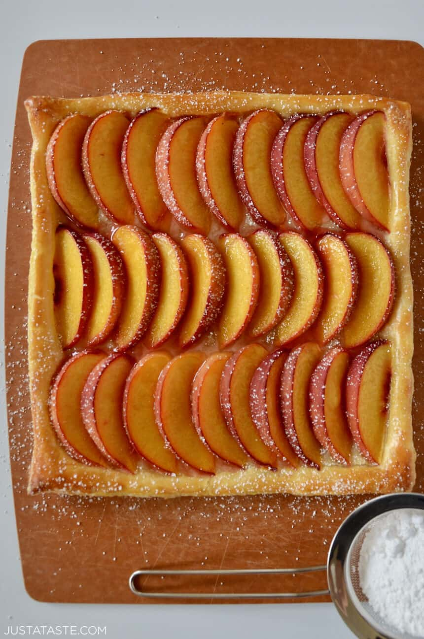 A top-down view of fresh peach slices dusted with powered sugar atop a buttery puff pastry crust.