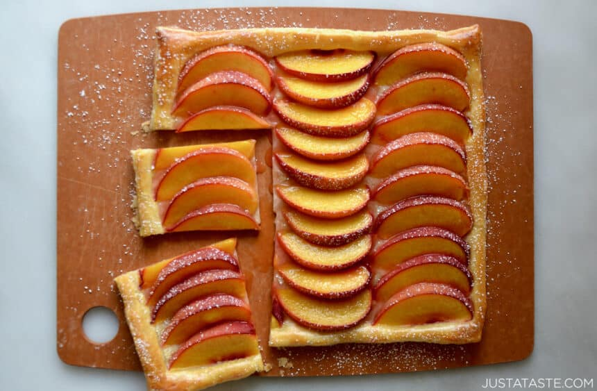 A top-down view of the best 5-ingredient peach tart on a wooden cutting board.
