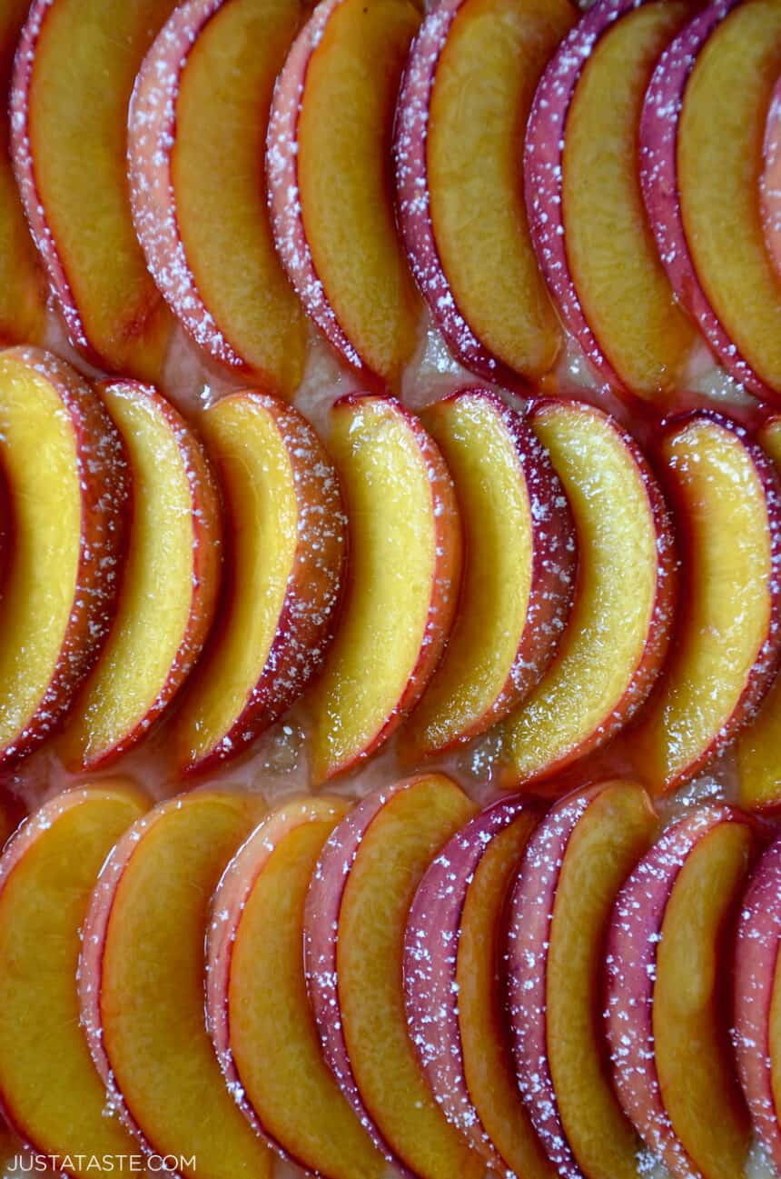 A closeup view of fresh peach slices in three perfect rows dusted with powdered sugar.