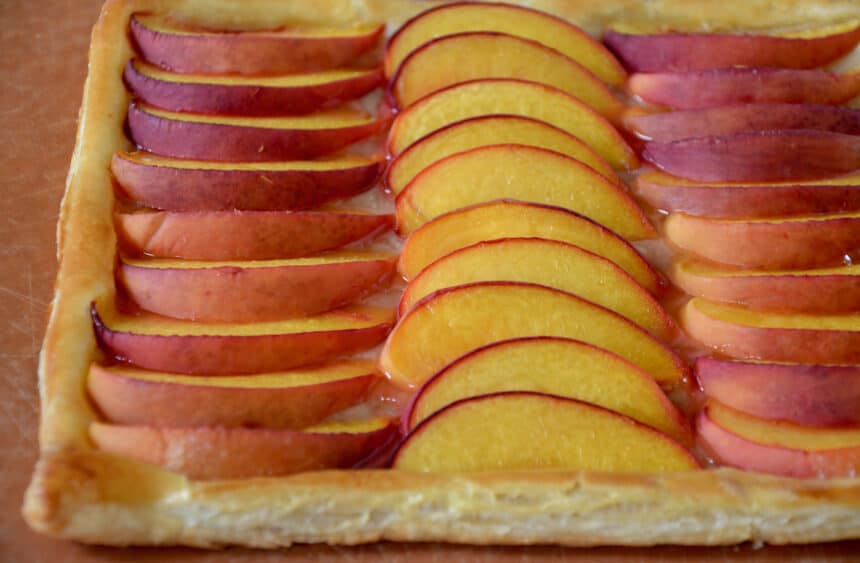 A golden brown pastry with slices of fresh stone fruit.