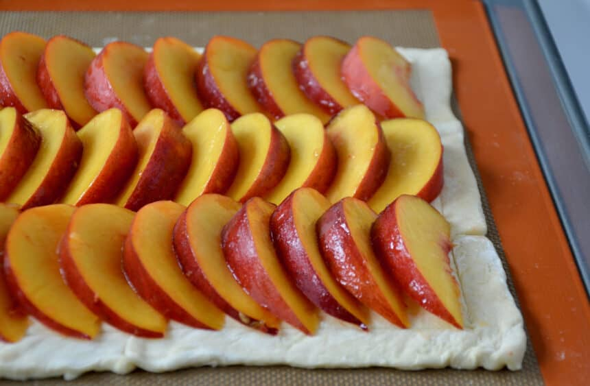 Puff pastry topped with rows of fresh stone fruit slices.