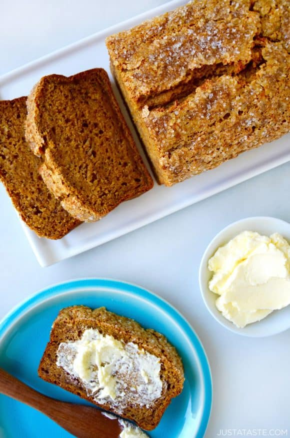 A loaf of pumpkin banana bread next to a slice on a plate slathered with butter